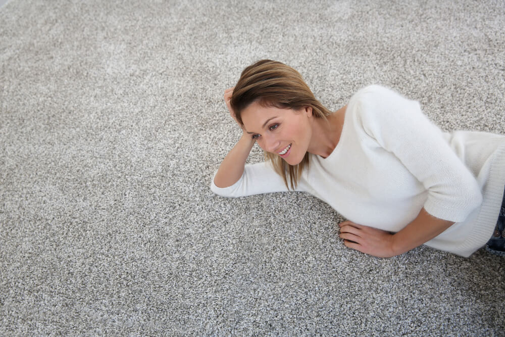 a woman laying on carpet cleaned by Ace Chem-Dry in Fort Collins